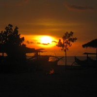 Just down from Kuta Beach, Bali. One of the last sunsets of 2009, I love the colours dancing off the water behind the boats. The fire on the beach was built by a local as his friends gathered near the hut to the left for some barbeque and drinks.